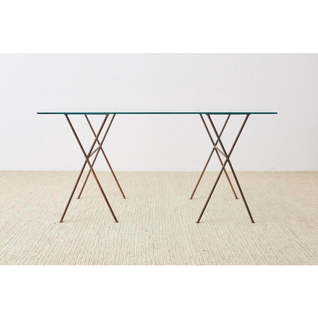 Unique Mid-Century Modern glass dining table or writing table desk. Featuring iron X form bases or sawhorse style...