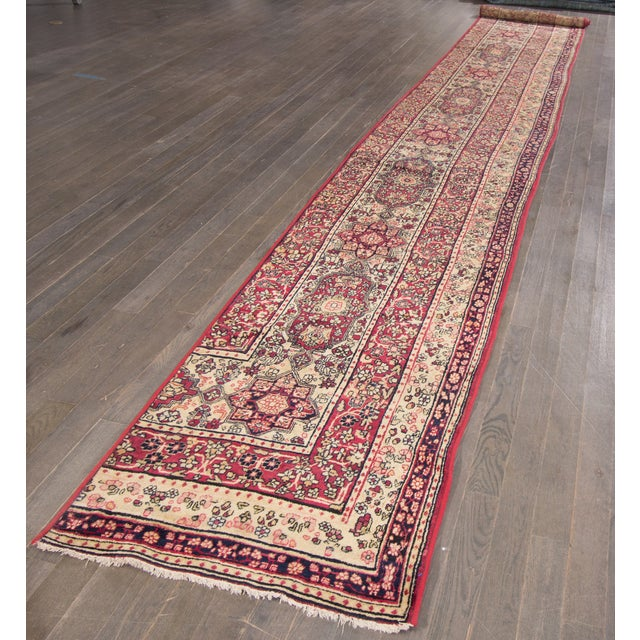 A 19th-century antique hand-knotted Kerman runner with a floral design. This is a fragment of a room size rug. This rug...