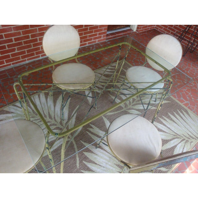 Versatile vintage wrought iron patio table with four chairs, attributed to Maurizio Tempestini for Salterini. The set...