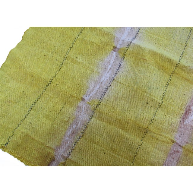 This eye catching vintage yellow mudcloth textile will add a unique pop of color to your space. The color is a bright...
