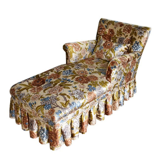 Long upholstered chaise longue sofa with arms. Upholstered in a velvet floral pattern of blue, orange, cream and yellow....