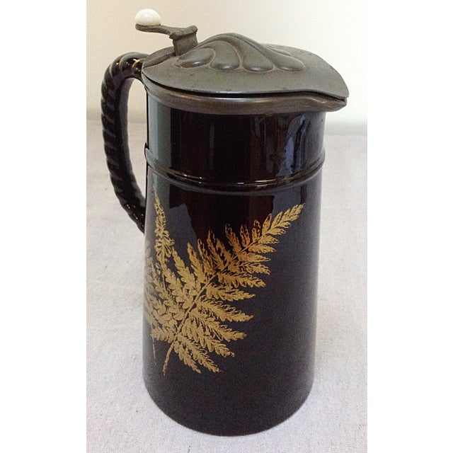 Antique stoneware pitcher. This black and gold piece features a fern decoration and a pewter lid.