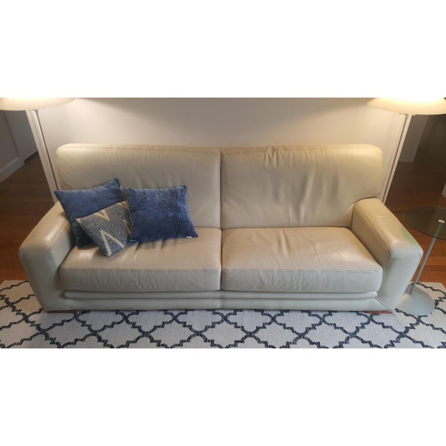 """A gently used Roche Bobois leather sofa from the 2000s. 86"""" long x 33"""" tall x 40"""" deep. Beige color, wooden black feet...."""