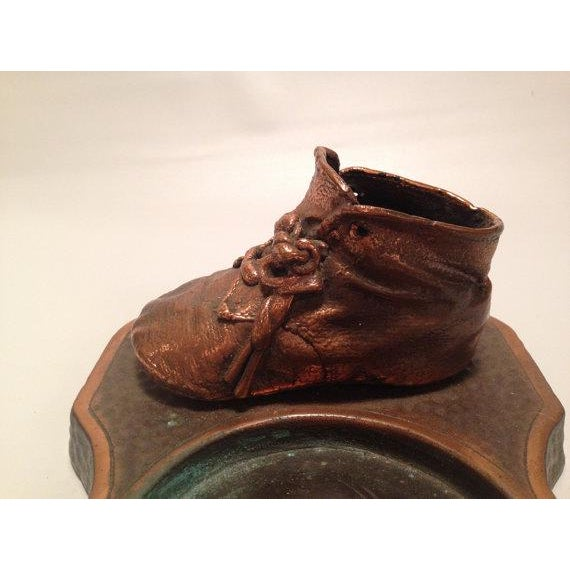 This old school, original bronzed leather baby boot sits atop a copper/bronze tray, perfect for tossing your keys or loose...