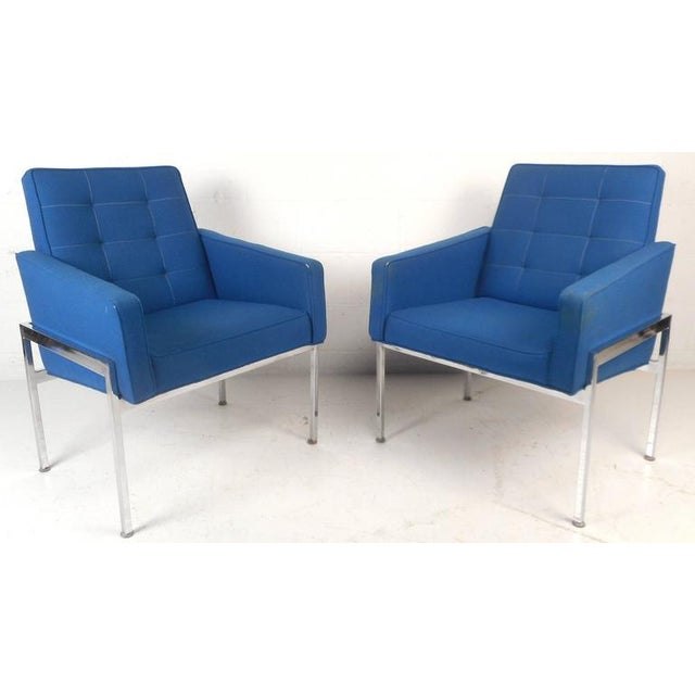 Elegant pair of Mid-Century Modern lounge chairs feature heavy chrome frames with royal blue tufted upholstery. Sleek...