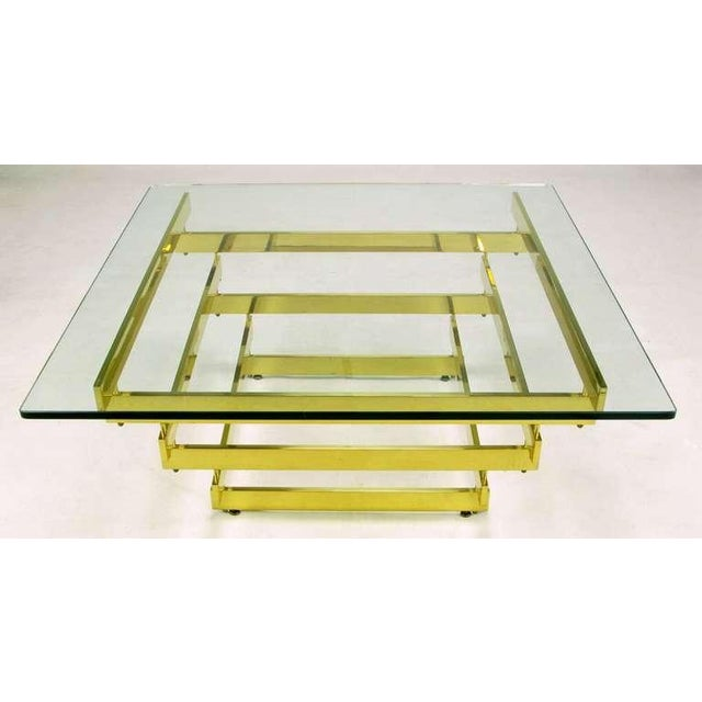 Elegantly inverted pyramidical shape, with five-eighths inch thick glass top, give this stacked brass bar coffee table...