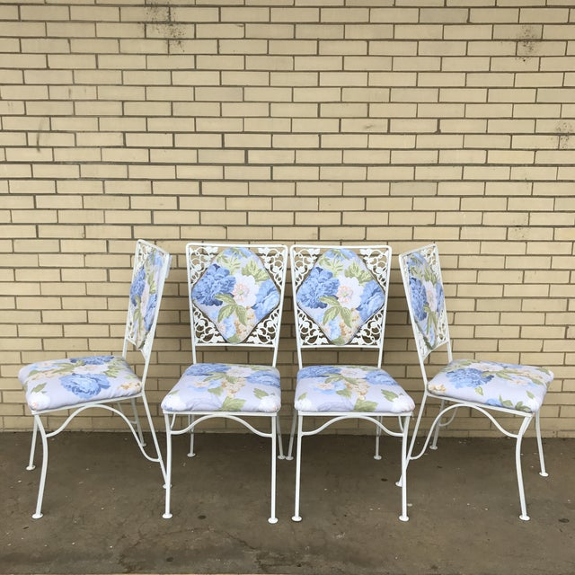 This set of iron chairs is beautiful! They feature upholstered curved backs surrounded by iron roses. The white paint has...