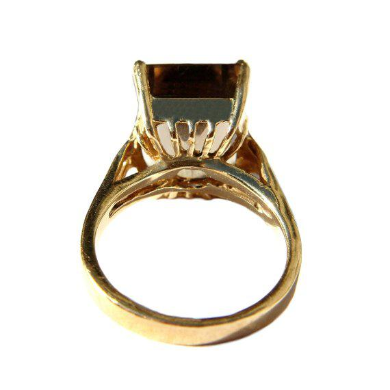 Circa 1980s 14K yellow gold ring prong set with an emerald-cut light yellow-brown smokey topaz stone. The top of the ring...