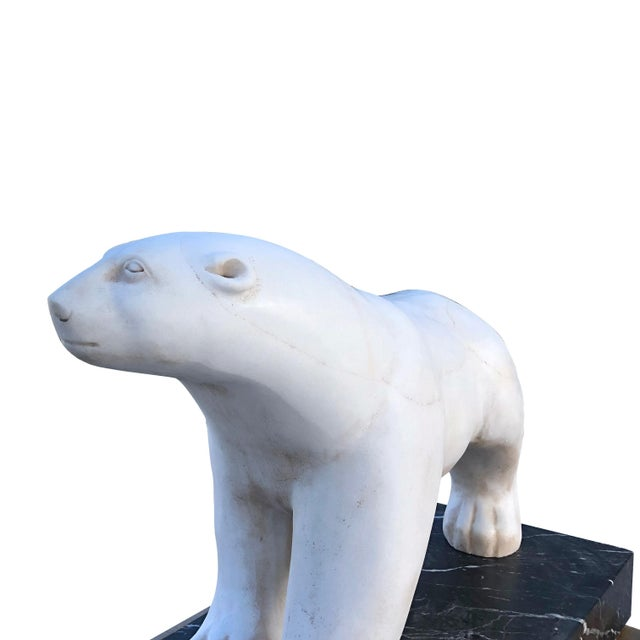 A hand carved white marble polar bear attributed to Francois Pompon on a rectangular black Marquina marble base. A similar...