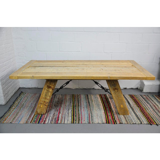 Solid salvaged industrial reclaimed wood dining table with metal elements. This farmhouse dining table is solidly...