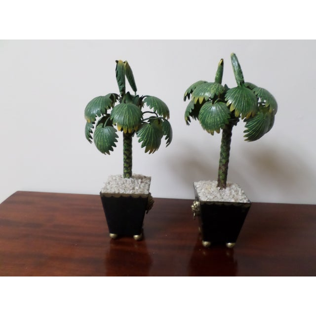 A colorful pair of miniature hand-painted tole palm tree topiaries in Regency style black pots with gilt lions head ring...