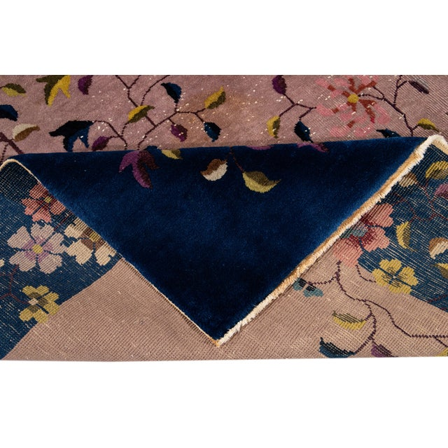 Beautiful antique Chinese Art Deco rug, hand-knotted wool with a pink rose field. This rug has a navy-blue frame and...