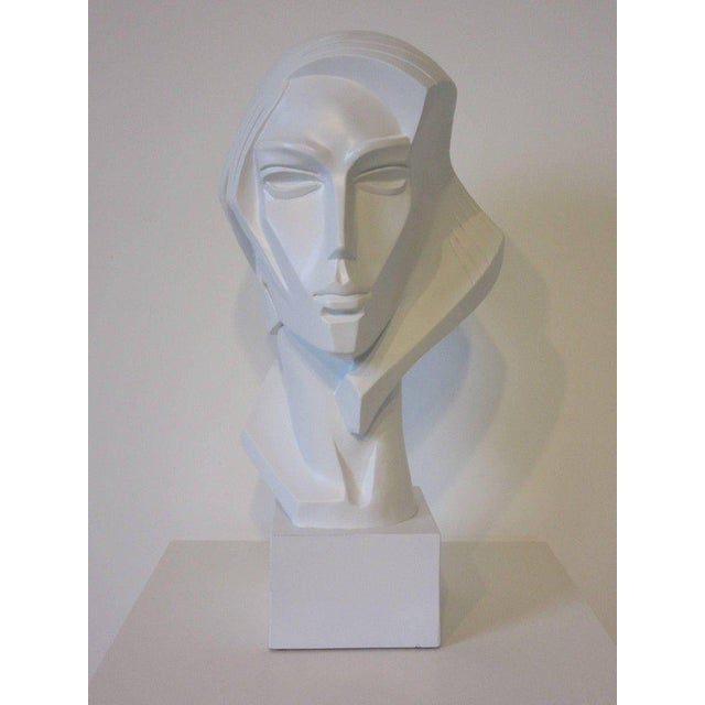 A large plaster female bust in the 1980s vibe reminiscent of Studio 54 in satin white on a wooden base, signed to the back...