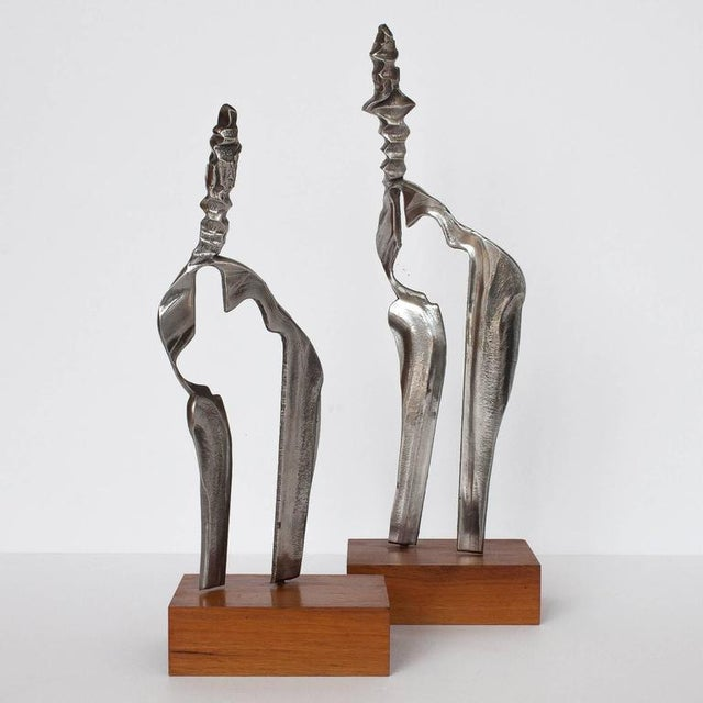 Set of two cast aluminum modernist abstract sculptures mounted on walnut wood stands. Unique Brutalist and figurative...