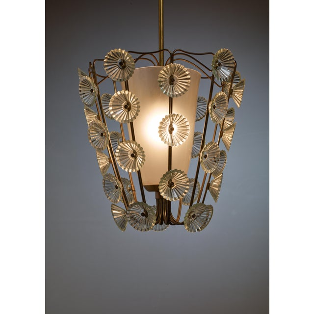 A rare model 1304 pendant lamp by Lisa Johansson-Pape for Orno. The lamp is made of an opaline glass shade in a brass...