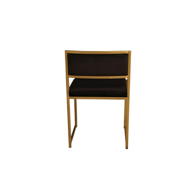 The Carlyle Side Chair features a sleek iron frame with a matte brass finish and black velvet upholstery on the seat and...