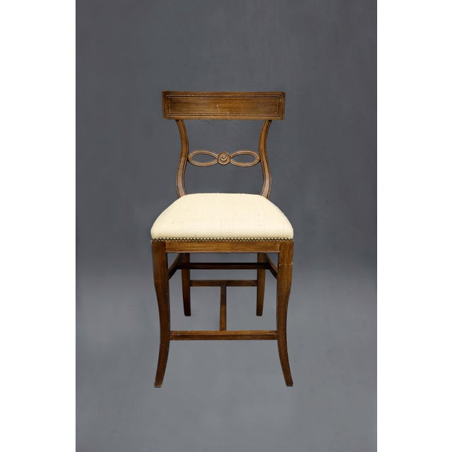 This dark wood counter stool with nature raffia covered seat features a delicate back with knotted rope design.