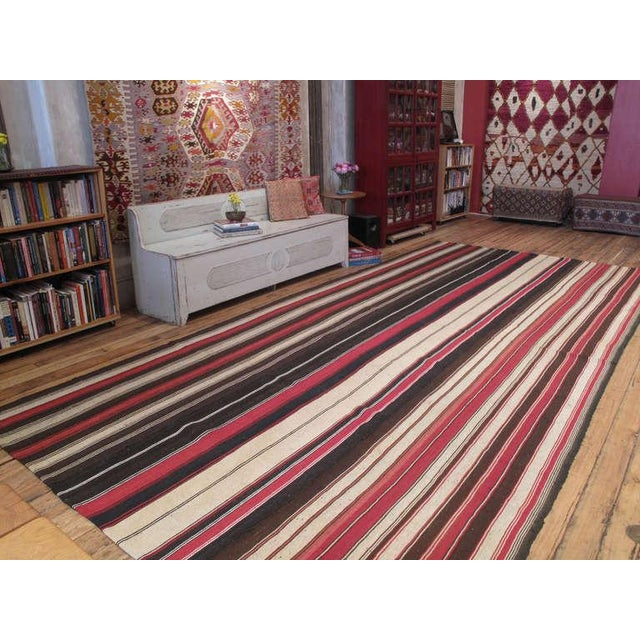 A large tribal floor cover, woven with goat hair in natural tones and red stripes. Very high quality weaving in excellent...