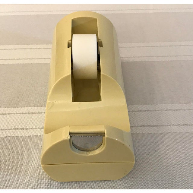 Great design on this Italian tape dispenser in a butter yellow color. It is weighted with something that sounds like sand.