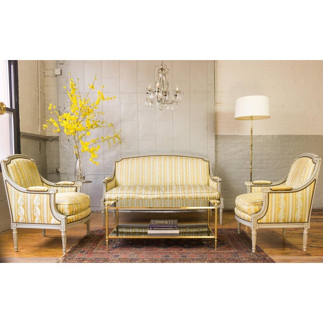 Pair of Louis XVI style armchairs with grey patinated and carved wooden frame upholstered in a striped silk fabric. The...