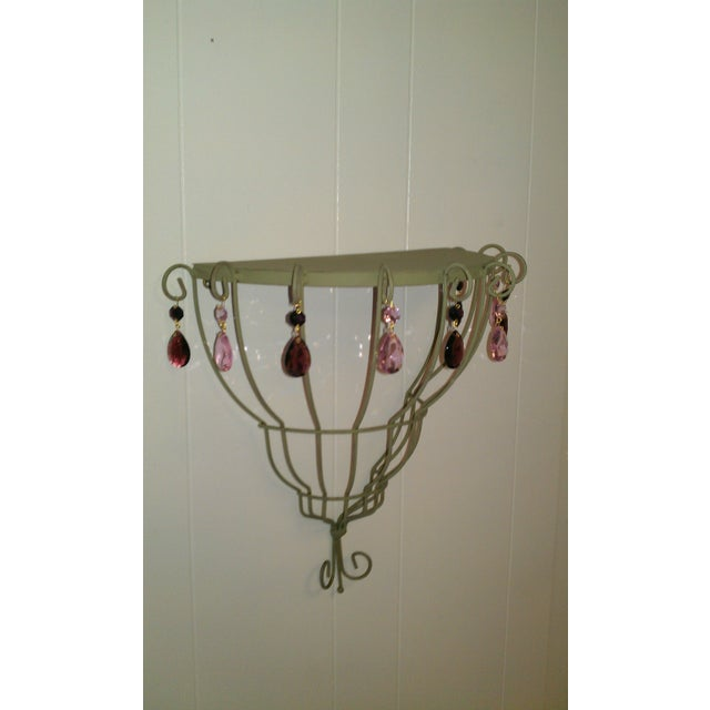 A beautiful accent shelf to display your special trinkets. This metal shelf has been updated in soft green hue with pink...