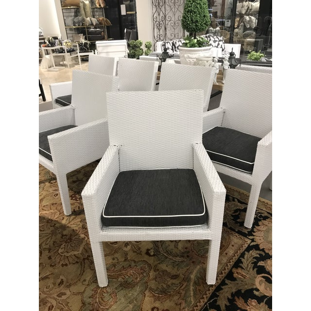 Set of six arm resin wicker dining chairs by Frontgate. These chairs were used for one season and come with custom...
