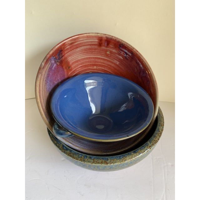 Set of three beautiful rustic pottery bowls in assorted glazed tones and textures. Two larger serving or decor bowls and...