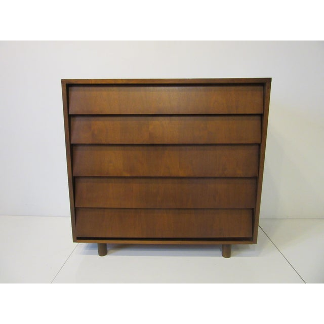 A walnut dresser with slanted front drawer design and top back lip detail sitting with lower legs and having five roomy...