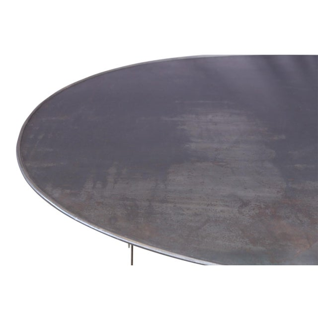 Oval hand-forged steel table with rounded edge raised-rim top. Ideal for both outdoor and indoor dining. This table is a...