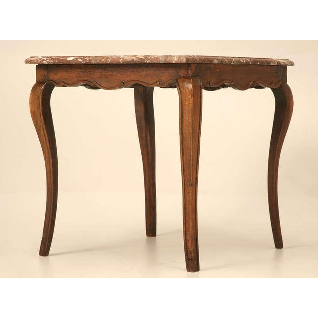 Dating to 1750, this Louis XV cherrywood table offers graceful legs, a scalloped apron and an outstanding naturally veined...