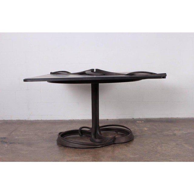 A forged steel and carved stone dining center table by Albert Paley. Stamped PALEY 1982. Published: Lucie-Smith, The Art...