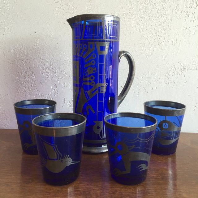 Unique ice tea, cocktail mixer set in cobalt blue glass with a silver Aztec design motif. The images appear to be hand...