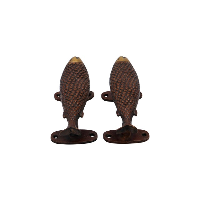A pair of red colored brass fish door handles or cabinet pulls. Hollywood Regency in style, with intricate carving...