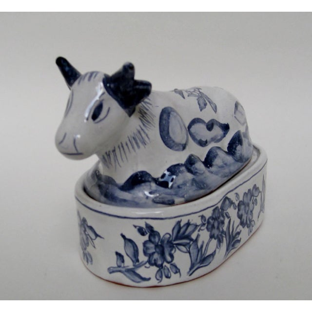 Hand-painted Portuguese ceramic country-style lidded container in the shape of a cow, accented with blue floral designs on...