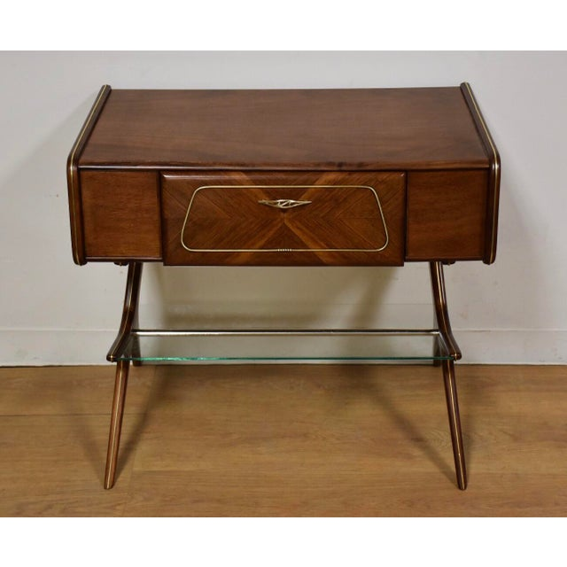 A brilliantly designed mid century modern rare walnut and brass table with a single drawer and lower glass magazine rack....