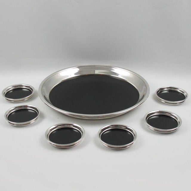 Elegant Mid-Century modernist barware set, comprising a round serving or bar tray and six coasters, manufactured by F.B....