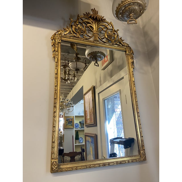This is a beautiful vintage Regency-style mirror with beautiful intricate detailed carvings. A tall portrait form mirror...