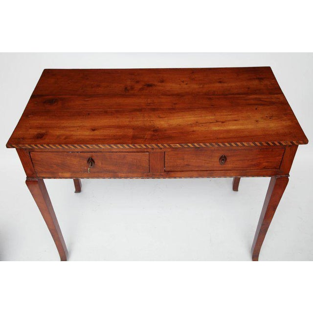 Cherry table with two drawers, parquetry border, finished back, carved wood escutcheons and tapered legs, Italy, circa...