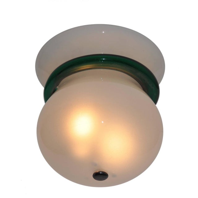 Internally frosted flush mount with a deep green melded band. The flush mount fits two E27 light bulbs. Original hardware....