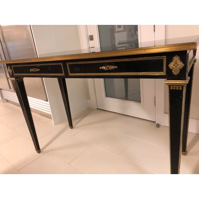 Handsome contemporary neoclassical style console by Ralph Lauren Home. Brass hardware and trim with a smoke mirrored top....