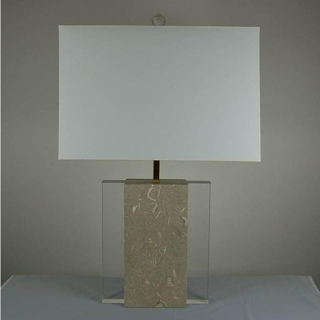 Two thick slabs of polished fossil stone with a GREENISH hue envelope a slab of Lucite. A monumental statement both...