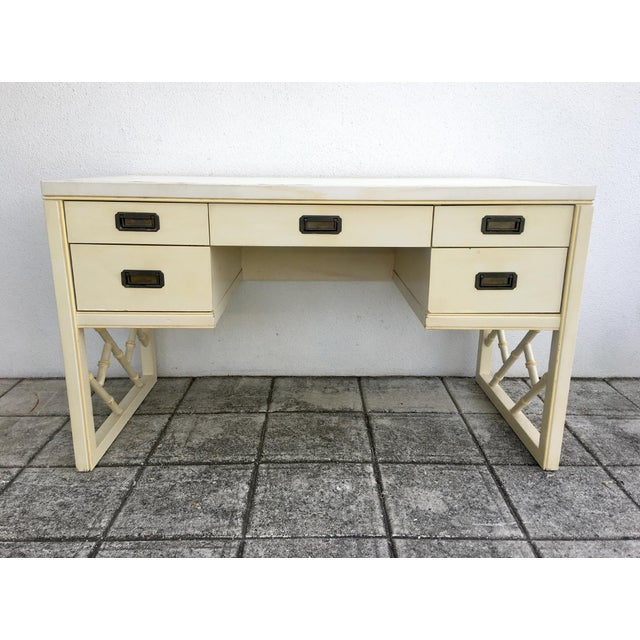 Vintage Regency campaign style desk with faux bamboo fretwork legs. Features an off white leather gold trim top, 2 drawers...