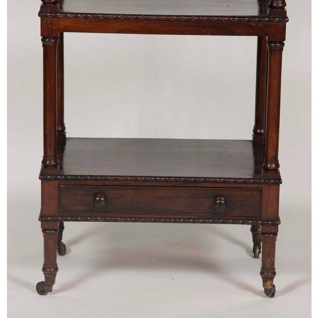With 3/4 gallery and bead and reel carved edge top over three conforming shelves and a drawer, raised on circular legs...