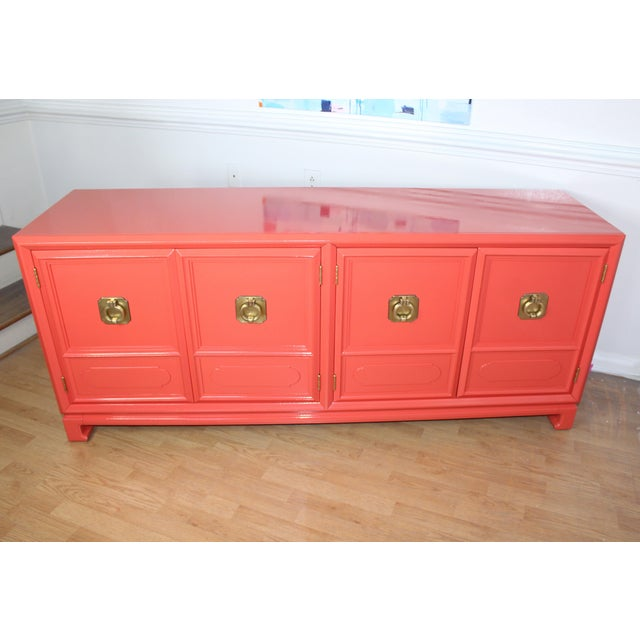Lacquered High Gloss Orange chinoiserie style Thomasville credenza with large stunning brass handles. Three drawers on the...