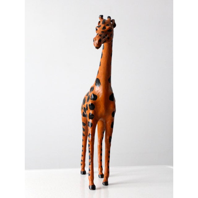 This is an antique leather giraffe sculpture. The hand-crafted figure features beautifully painted leather with glass eyes.