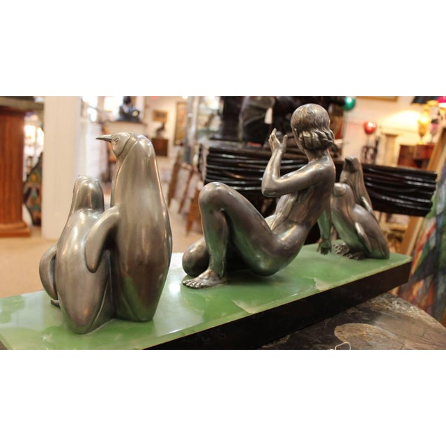 Classic Art Deco silvered bronze of female dancer with penguins. The center figure is a semi nude athletic female flaked...