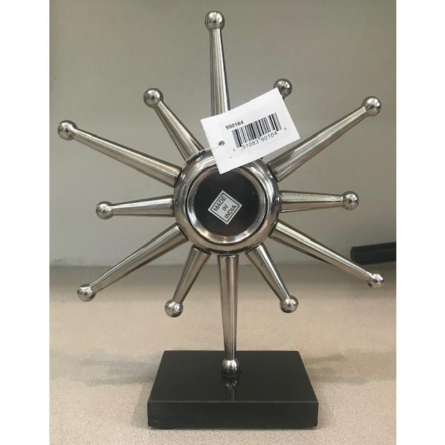"""Sitting on a black granite base, the star shaped frame holds a round clock. 9""""L X 3""""W X 10.5""""H"""