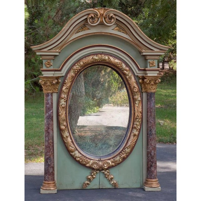 This superb early 19th century Italian architectural overmantel oval mirror is green painted with partial gilt. The curved...