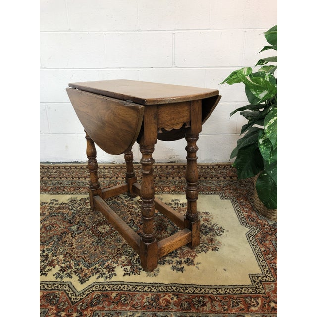 """Beautiful antique drop leaf table. Very rare find! Marked """"Made from 15th Century Roof. Timbers of Norwich Cathedral"""". The..."""