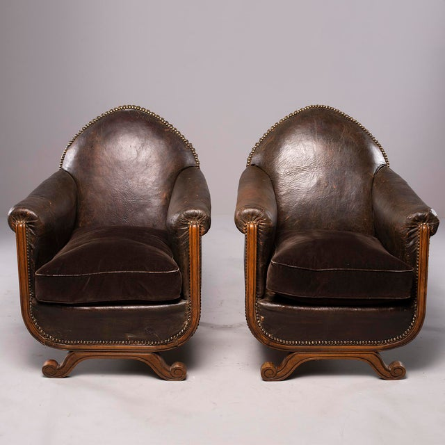 Circa 1930s pair of French leather club chairs with wood frames. Camel back chairs with rolled arms, exposed wood frames,...